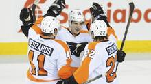 Philadelphia Flyers centre Brayden Schenn (10) celebrates his second period goal with defenceman Andrej Meszaros (41) and defenceman Luke Schenn (22) against the Calgary Flames at Scotiabank Saddledome. (Candice Ward/USA Today Sports)