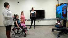 From left, Cheryl Peters, Jillian, 7, and Lauren, 9, play a game being developed for kids with cerebral palsy while the game's developer, Elaine Biddiss, looks on. (Deborah Baic/The Globe and Mail)