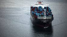 A container ship prepares to pass under the Lions Gate Bridge in Vancouver. (Rafal Gerszak for The Globe and Mail)