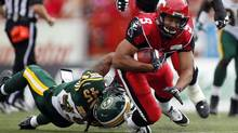 Edmonton Eskimos' Damaso Munoz, left, tackles Calgary Stampeders' Jon Cornish, during first half CFL football action in Calgary, Alta., Monday, Sept. 2, 2013. The two teams meet again in Friday CFL action. (JEFF McINTOSH/THE CANADIAN PRESS)