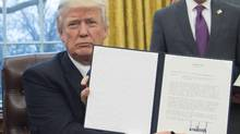 President Donald Trump holds up an executive order withdrawing the U.S. from the Trans-Pacific Partnership in the Oval Office on Jan. 23, 2017. (SAUL LOEB/AFP/Getty Images)