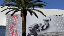 Workers set up a giant canvas of the official poster of the 66th Cannes Film Festival featuring Joanne Woodward and Paul Newman, photographed during the shooting of A New Kind of Love, on the facade of the Festival Palace in Cannes on May 13, 2013. (ERIC GAILLARD/REUTERS)