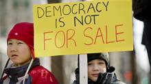 Two young children take part in a Montreal protest over the robo-call election scandal on March 11, 2012. (Graham Hughes/Graham Hughes/The Canadian Press)