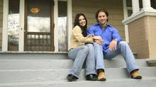 Young couple sitting in front of a new house. (Photos.com)