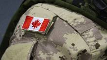 A Canadian flag sits on the shoulder of a member of the Canadian Forces in Trenton, Ont. (Lars Hagberg/THE CANADIAN PRESS)