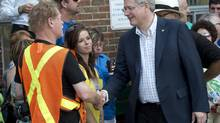 Prime Minister Stephen Harper meets residents while visiting the emergency centre Sunday, July 7, 2013 in Lac Megantic, Que., the day after a train derailed causing explosions of railway cars carrying crude oil. (Ryan Remiorz/THE CANADIAN PRESS)