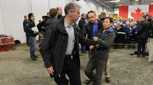 Li Xuejiang , of the People's Daily, China's largest newspaper, is hauled to the back of the room by RCMP as Stephen Harper answers questions while visiting Xstrata Nickel's Raglan Mine in the northern Nunavik region of Quebec on Friday, August 23, 2013. When staff did not recognize Li's request to answer a question he tried to take the microphone and a tussle erupted. (Sean Kilpatrick/THE CANADIAN PRESS)