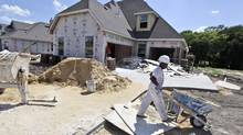 Workers finish up a house in Wylie, Texas. (LM Otero/AP)