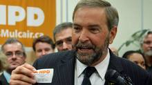 NDP MP Thomas Mulcair holds up his party membership card in his Montreal riding as he announces his bid to succeed Jack Layton as leader on Oct. 13, 2011.l (Ryan Remiorz/THE CANADIAN PRESS)