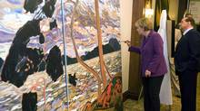 Italy's Prime Minister Silvio Berlusconi watches as German Chancellor Angela Merkel paints part of a bucolic picture during the G8 Summit at the Deerhurst Resort in Huntsville, Ontario, June 25, 2010. (Guido Bergmann/Reuters)