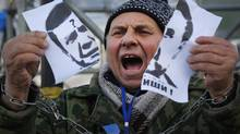"A demonstrator holds a torn portrait of Ukrainian President Viktor Yanukovych and shouts ""Coward!"" during a rally in support of Ukraine's integration with the European Union in the center of Kiev on Nov. 29, 2013. (Sergei Grits/AP)"