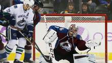 Colorado Avalanche goalie Semyon Varlamov, right, of Russia, makes a glove save of a redirected shot off the stick of Vancouver Canucks left wing Daniel Sedin, front left, of Sweden, as Avalanche defenseman Jan Hejda, back left, of the Czech Republic, covers in the first period of an NHL hockey game in Denver on Tuesday, Nov. 4, 2014. (David Zalubowski/AP Photo)