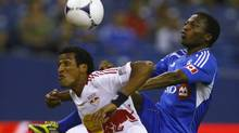 New York Red Bulls' defender Roy Miller (L) and Montreal Impact's midfielder Sanna Nyassi fight for the ball during the first half of their MLS soccer match in Montreal, May 19, 2012. REUTERS/Olivier Jean (Olivier Jean/Reuters)
