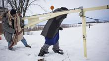Somali refugees Abdullahi Warsame, left, and Lul Abdi Ali slip under a roadblock in Noyes, Minn., to enter Canada on Sunday. (Ian Willms / The Globe and Mail)