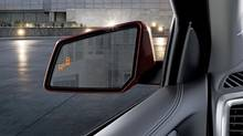 Blind-zone alerts light up in the left mirror to warn the driver about changing into the left lane. (General Motors)