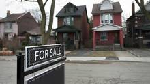 A 'for sale' sign stands in front of detached homes on Redwood Avenue in Toronto. (Darren Calabrese For The Globe and Mail)