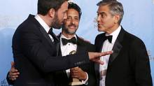 Producer and director Ben Affleck, left, talks with fellow Argo producers Grant Heslov, centre, and George Clooney at the 70th annual Golden Globe Awards in Beverly Hills, California Jan. 13, 2013. (LUCY NICHOLSON/REUTERS)