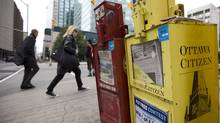 Pedestrians walk past a Ottawa Citizen newspaper box in downtown Ottawa. (Sean Kilpatrick)