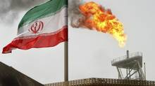 Gas flares from an oil production platform, with an Iranian flag in the foreground, at the Soroush oil fields in the Persian Gulf in this file photo. (RAHEB HOMAVANDI/REUTERS)