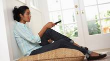 woman sitting on floor watching TV (Photos.com)