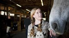 Collen Taylor (L) watching her daughter Hannah Taylor, 13, visiting horses in the stables before their riding lesson. (unknown)
