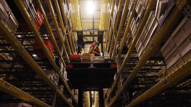 Associate Bonnie Joswick fills an order in her automated lift truck in the vast shoe section at the Macy's-Bloomingdale's fulfillment centre in Martinsburg, West Virginia Dec. 6, 2012. (Gary Cameron/Reuters)