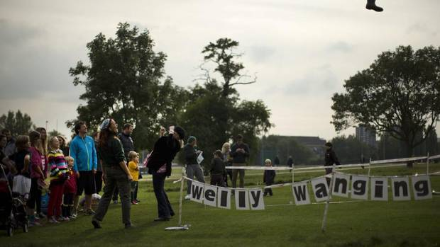 People have a go at 'welly wanging' during the Hampstead Heath Heritage Festival, a celebration of old England in London, Sunday, Oct. 7, 2012. (Matt Dunham/AP)