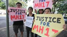 A small group of protesters stand outside the Russian embassy in Kuala Lumpur demanding action against those responsible for shooting down Flight MH17. (Iain Marlow/The Globe and Mail)