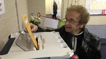 Sylvia Contover, 99, of Chelmsford, Mass., places her vote for president in the ballot box during early voting. (Alana Melanson/The Sun of Lowell, Mass.)