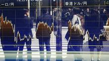 People are reflected on the electronic board of a securities firm in Tokyo, on March 17, 2017. (Koji Sasahara/AP)