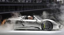Porsche CEO Matthias Mueller, left, and former rally driver Walter Roehrl arrive in the Porsche 918 hybrid sports car at the 65th Frankfurt Auto Show in Frankfurt, Germany last week. The Porsche 918 Spyder e-hybrid has 887 hp and will have fuel consumption of between 3.0 and 3.3 litres/100 km. (Frank Augstein/AP Photo)