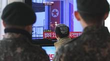 "South Korean army soldiers watch a public TV reporting a news about North Korea's rocket launch at Seoul Railway Station in Seoul on Wednesday. North Korea fired a long-range rocket Wednesday in its second launch under its new leader, South Korean officials said, defying warnings from the U.N. and Washington only days before South Korean presidential elections. The letters at a screen read ""Presidential house convened an emergency meeting of the National Security Council."" (Ahn Young-joon/AP)"