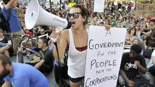 """A woman with a bullhorn addresses fellow demonstrators with """"Occupy Boston"""" group as they briefly blocked Summer Street in Boston, Monday afternoon, Oct. 10, 2011. (JOSH REYNOLDS/AP)"""