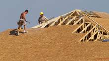 In this file photo, carpenters work to enclose a roof on a home being built in Sprinfield, Ill. (Seth Perlman/AP)