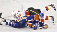 Calgary Flames' Lee Stempniak and Edmonton Oilers' Ryan Smyth battle for the puck during second period NHL hockey action in Edmonton, Alta., on Saturday April 13, 2013. (The Canadian Press)