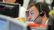 A trader checks screen data at the IG Index trading floor in London June 11, 2011. (Reuters)