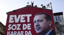 A man stands at the top of an Yes campaign billboard bearing the portrait of Turkish President Recep Tayyip Erdogan on Thursday in Istanbul. (Bulent Kilic/AFP/Getty Images)