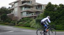 A cyclist rides past a $13.898-million home in the Point Grey area of Vancouver on Jan. 15, 2013. (Jeff Vinnick For The Globe and Mail)