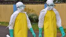Health workers wearing protective gear go to remove the body of a person who is believed to have died after contracting the Ebola virus in the city of Monrovia, Liberia, on Aug. 16. (Abbas Dulleh/AP)