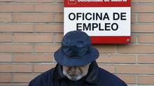 A man looks down as he waits in line to enter a government-run employment office in Madrid. (SERGIO PEREZ/REUTERS)