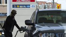 A woman pumps gas in Toronto on Tuesday, May 10, 2011. (Nathan Denette/Nathan Denette/THE CANADIAN PRESS)