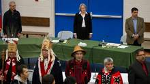 Panel members stand with Haisla First Nation hereditary chiefs during the opening day of hearings for the Northern Gateway project in Kitamaat Village, B.C., on Jan. 10. (DARRYL DYCK/THE CANADIAN PRESS)