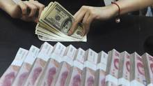 U.S. dollars and Chinese yuan. (JIANAN YU/REUTERS/Stringer/Files)