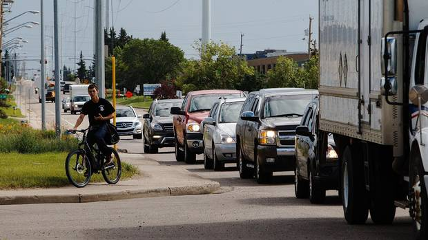 Forget trying to negotiate traffic like this – one cyclist prefers to take the sidewalks at 97 Street and 51 Avenue in Edmonton (Codie McLachlan for the globe and mail)