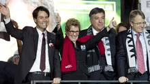 Kathleen Wynne stands with Ontario Liberal leadership candidates Eric Hoskins, Charles Sousa and Gerard Kennedy, all of whom offered their support to Wynne. (Peter Power/The Globe and Mail)