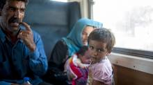 A migrant family sit on a train heading for Serbia at the new transit center for migrants at the border between Greece and Macedonia on September 3, 2015. (ROBERT ATANASOVSKI/AFP/Getty Images)