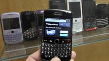 A BlackBerry device is shown in front of products displayed in a glass cabinet at the Research In Motion offices in Waterloo in this file photo. (MIKE CASSESE/REUTERS)