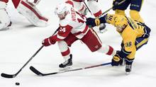 Detroit Red Wings right wing Gustav Nyquist (14) and Nashville Predators left wing Viktor Arvidsson (38) chase the puck during the second period of an NHL hockey game in Nashville, Tenn., on Feb. 4, 2017. (Mark Zaleski/THE ASSOCIATED PRESS)
