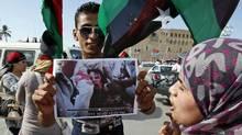 A man holds a photo Moammar Gadhafi's body as Libyan's celebrate the dictator's death in Tripoli on Oct. 20, 2011. (Abdel Magid al-Fergany/AP)