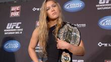 (Rowdy) Ronda Rousey shows off her UFC bantamweight championship belt, on Dec. 6, 2012 in Seattle. (Neil Davidson/THE CANADIAN PRESS)